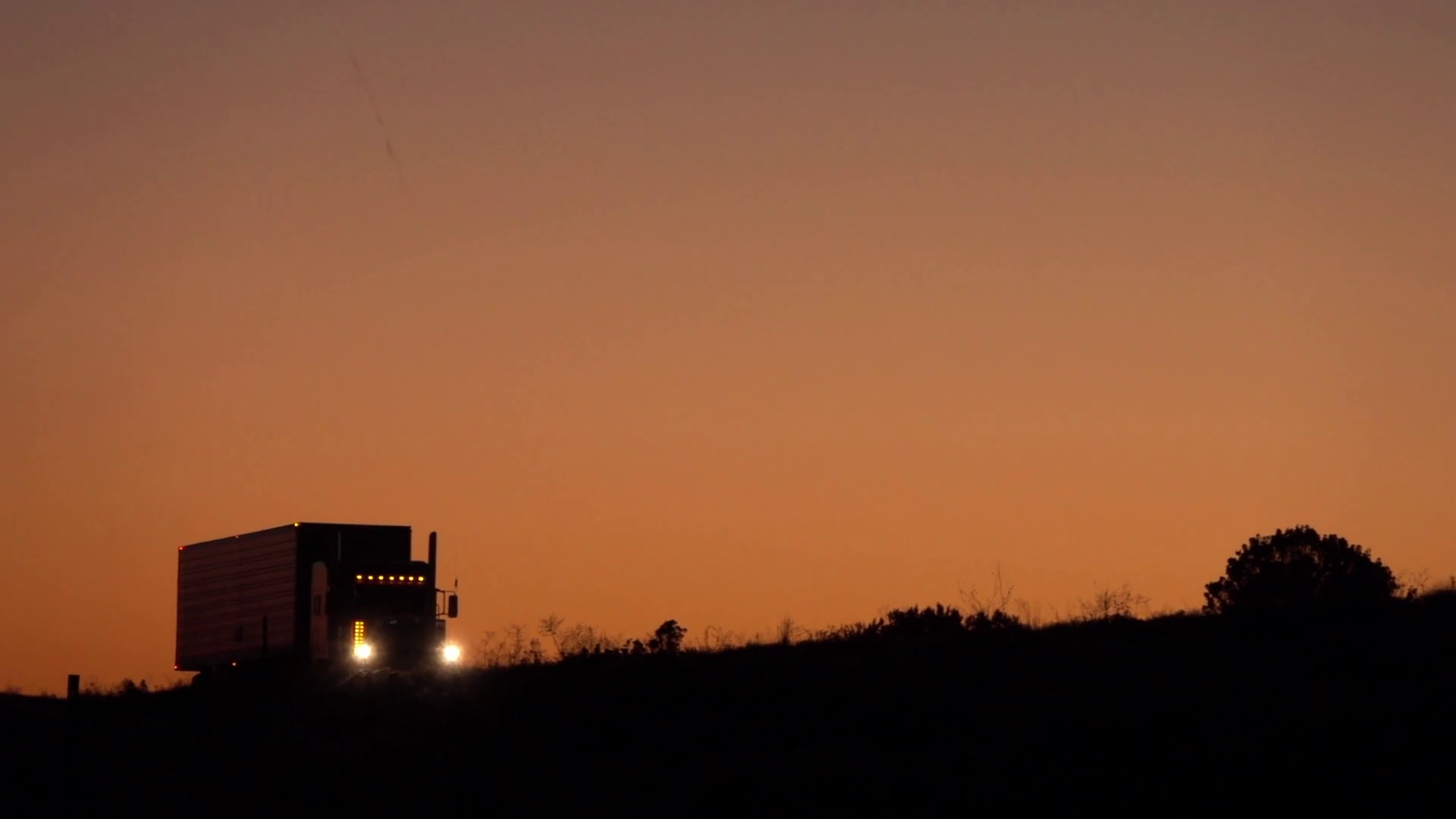 videoblocks-slow-motion-silhouetted-semi-trailer-truck-driving-along-the-highway-in-the-dark_b-mo5cpag_thumbnail-full01